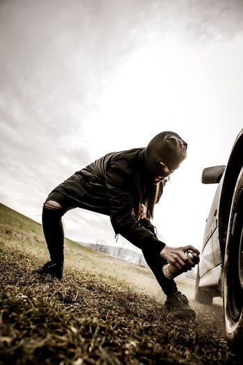 Disguised Woman Spraying Color On Tire Of Car