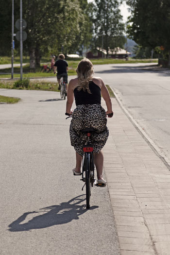 Rear view of women riding bicycle on road