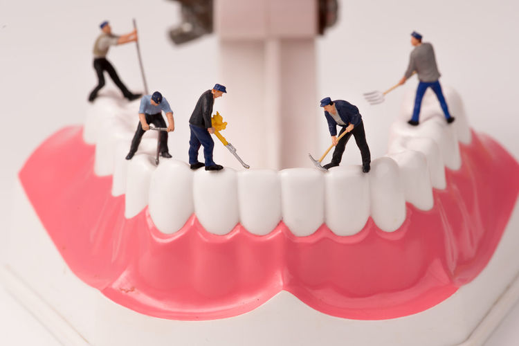 Miniature men working on dentures