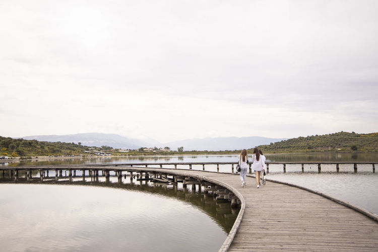 Rear view of people on lake against sky