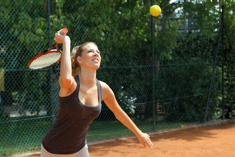 Female athlete playing tennis on court against trees