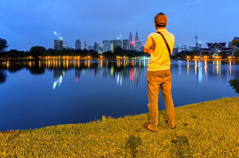 Rear view of man standing at riverbank against illuminated cityscape at night