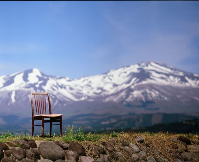 Close-up of chair with snowcapped mountain range in background