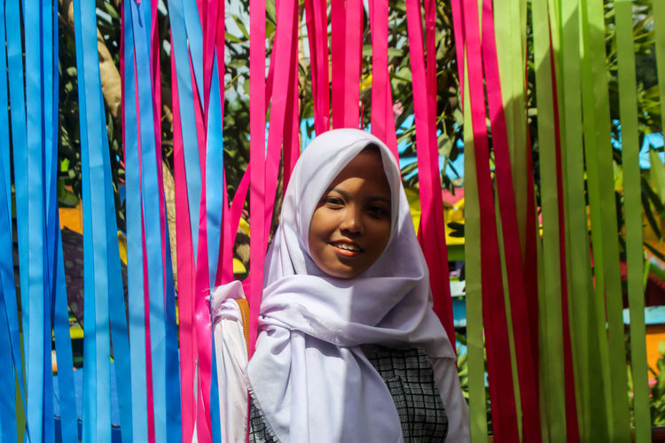 Portrait Of Happy Teenage Girl In Traditional Clothing Standing Amidst Multi Colored Decoration