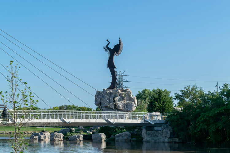 Statue by bridge against clear sky