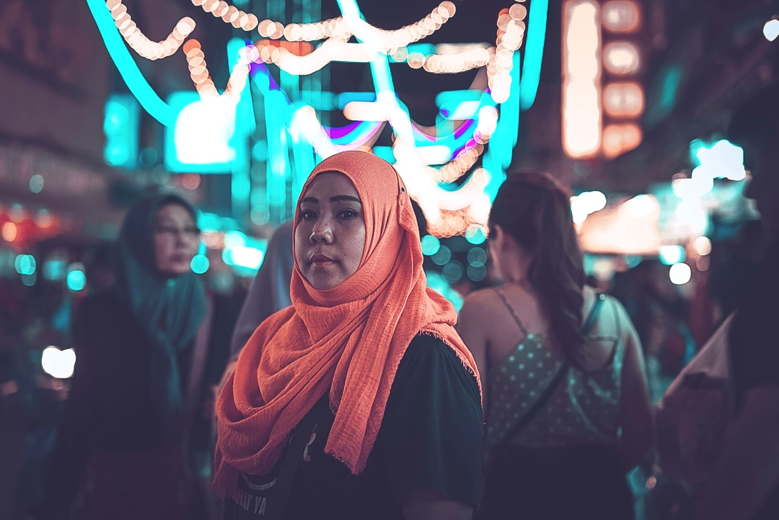 illuminated, night, focus on foreground, lifestyles, incidental people, real people, women, leisure activity, standing, portrait, group of people, people, emotion, adult, lighting equipment, young adult, front view, waist up, clothing, young women, nightlife, light, scarf