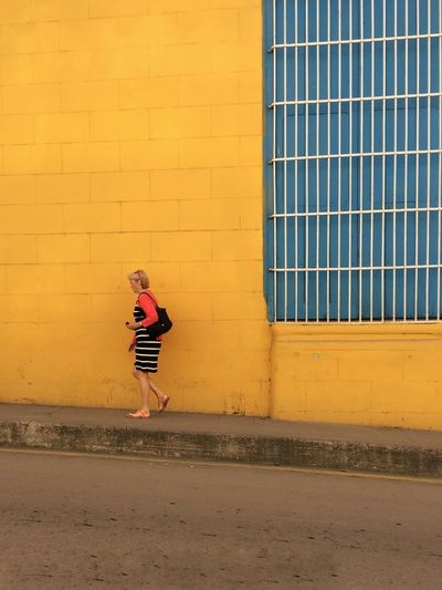 Señora caminando frente a una pared amarilla Blue Building Exterior Built Structure Full Length One Girl Only One Person Outdoors People Street Streetphotography Window Yellow