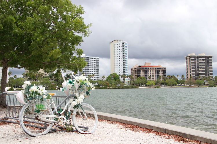 Bicycle by river against buildings and sky in city