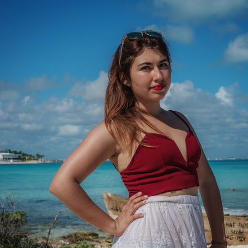 Beautiful young woman standing by sea against sky