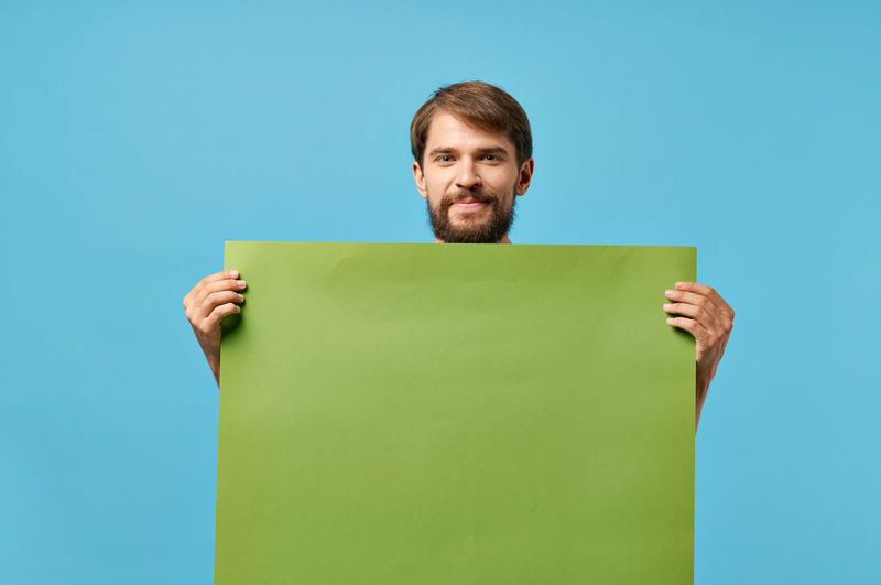 Portrait of smiling man standing against blue background