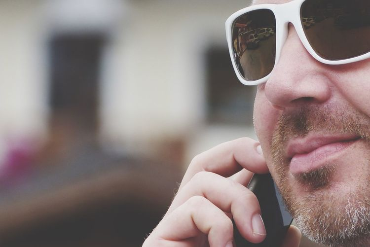 Close-up of man wearing sunglasses using phone outdoors