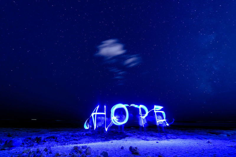 Illuminated hope text made by light painting at beach against star field