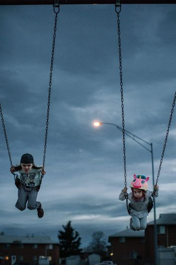 Swinging siblings Hanging Sky Swing Cloud - Sky Outdoors Childhood Low Angle View Leisure Activity Real People One Person Tree Chain Swing Ride Christmas Decoration Day Carousel People