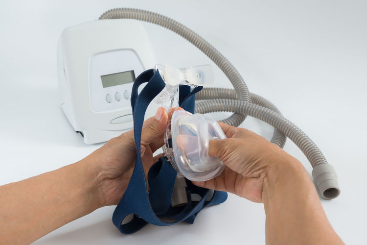 Man hands reassembly Softgel cushion to a mask frame ,white background,selective focus. Cpap Continuous positive airway pressure system includes of main unit,nasal mask,patient tube and headgear,cleaning concept. Sleep Apnea Cleaning Equipment Disorder Filter Medical Equipment Snoring Tube Cpap Cushion Man Hands Mask Nasal Obstructive Sleep Apnea