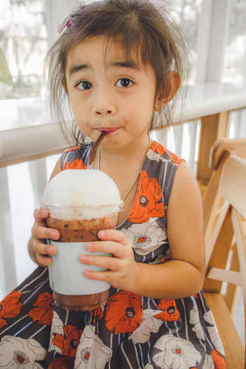 Portrait of cute girl holding ice cream at home