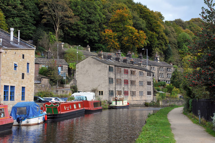 canal boats and houses in hebden bridge Hebden Bridge Architecture Building Exterior Built Structure Canal Day Houseboat Nature Nautical Vessel No People Outdoors River Sky Town Transportation Tree Water Waterfront