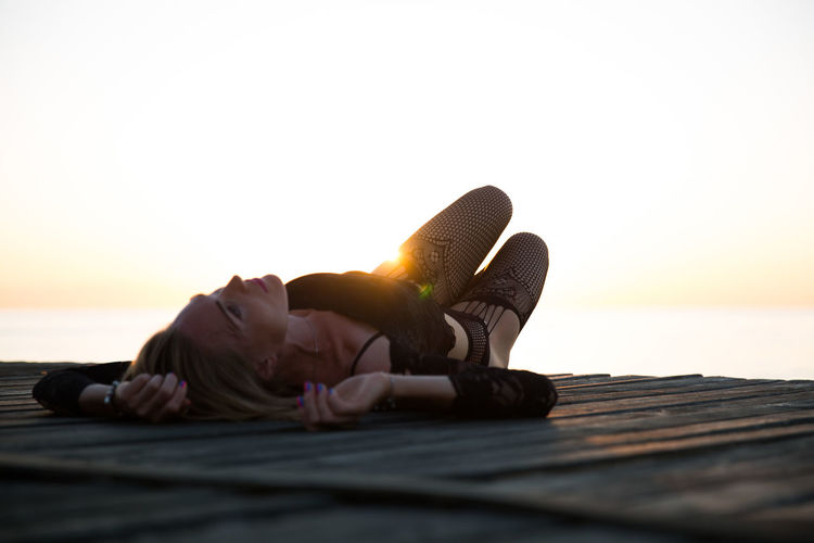 Sensuous woman lying on pier over sea against sky during sunset