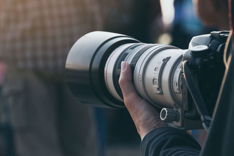 Closeup Telephoto lens with camera on hand Camera DSLR Working Camera - Photographic Equipment Cinematography Close-up Digital Camera Equipment Handle Holding Human Hand Journalism Lens Lens - Optical Instrument Operation Outdoors People Photographer Technology Telephoto Lens Video