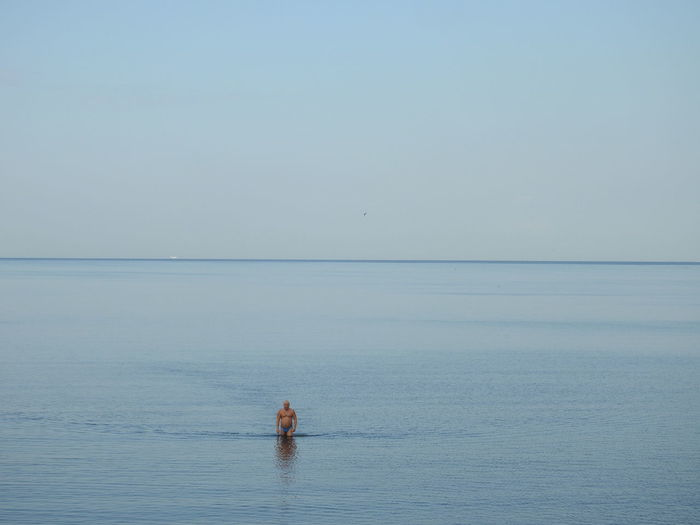 Distant view of man standing in sea against sky