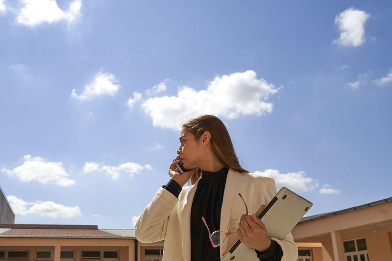 Confident beautiful business lady talking on the phone, with the blue sky as background.