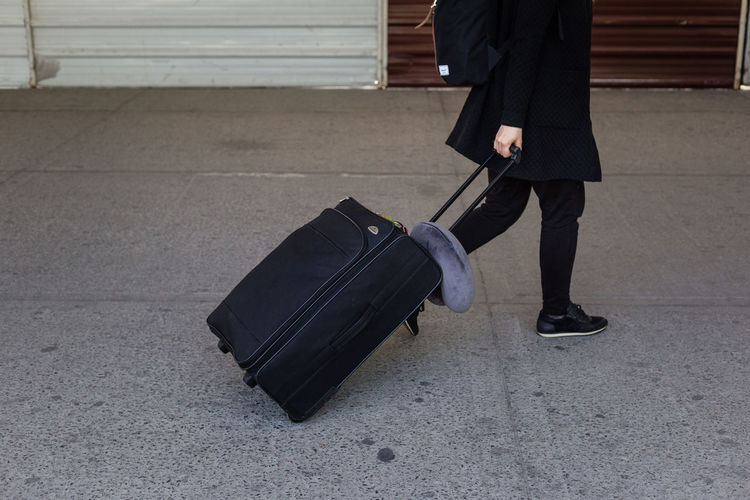 Low section of man with luggage walking on footpath