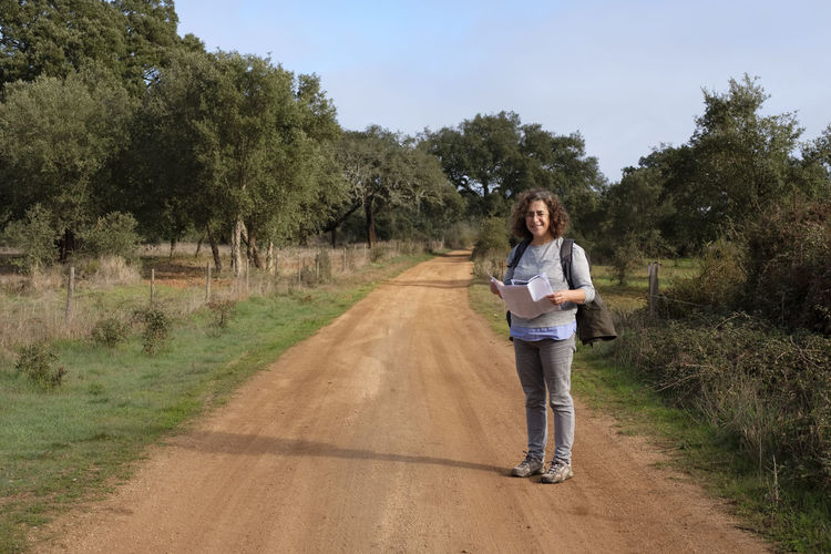 Full length portrait of woman standing on dirt road
