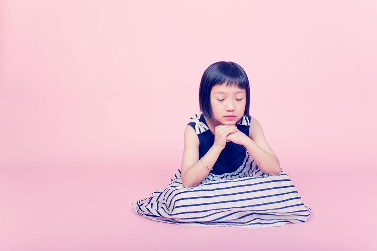 Girl with eyes closed sitting against pink background