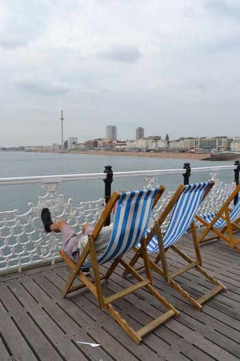 Man sitting on deck chair at brighton beach