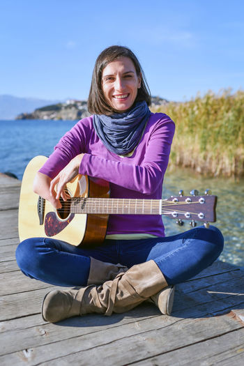 Portrait woman playing guitar while sitting on pier by lake