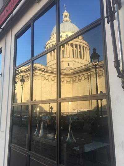 Low angle view of building seen through glass window