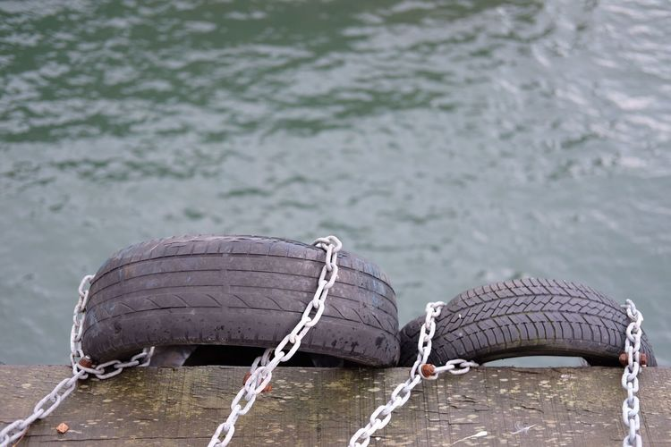 Close-up of tires on pier