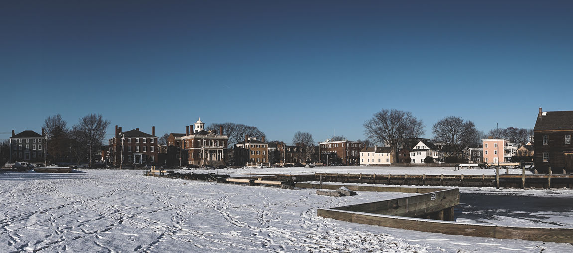 Panoramic View Of Snow Covered Landscape In City Against Clear Blue Sky