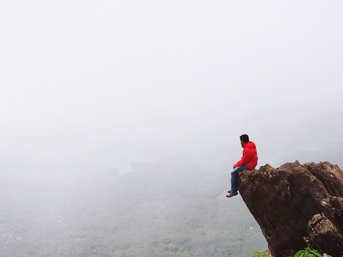 Man sitting on cliff against sky during foggy weather