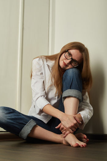 Young woman sitting against wall at home