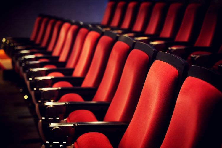 Empty red seats in row at movie theater