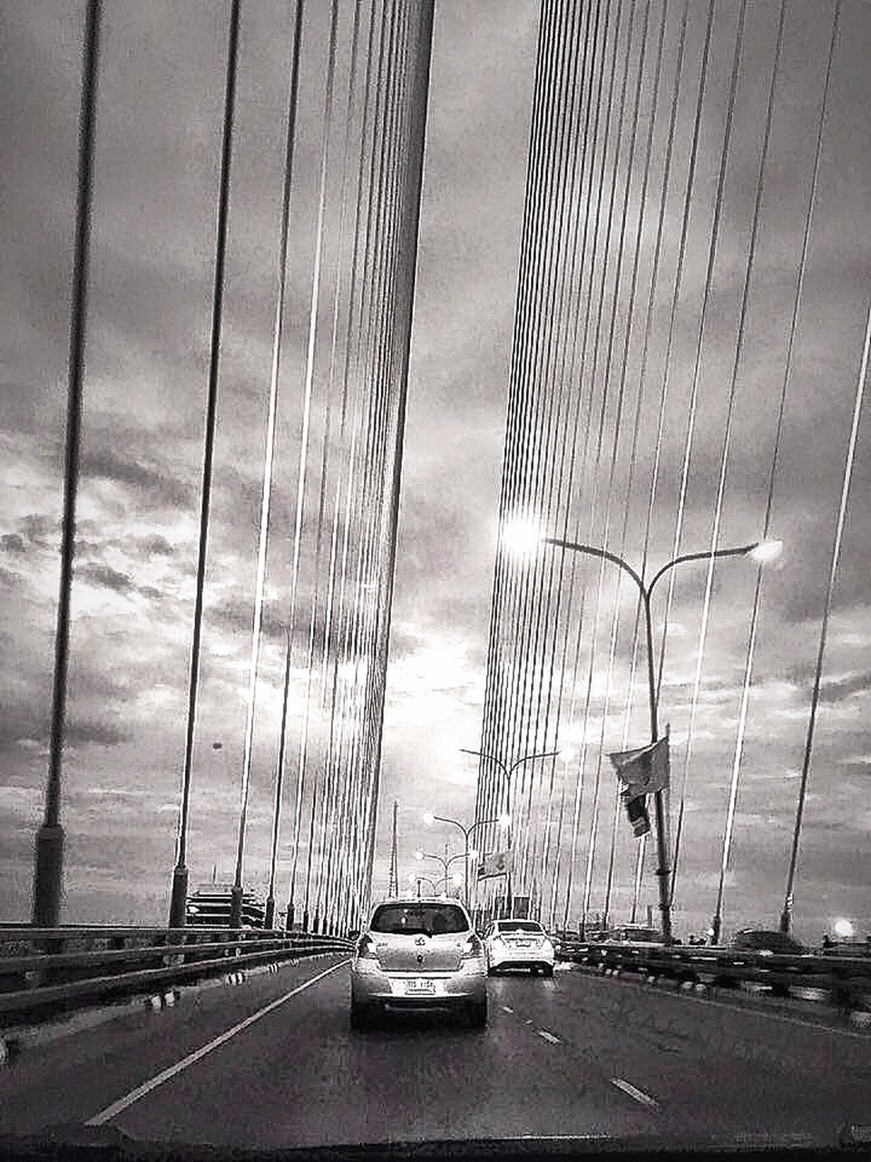 car, transportation, suspension bridge, land vehicle, bridge - man made structure, mode of transport, sky, traffic, road, cloud - sky, the way forward, street, connection, city, architecture, outdoors, built structure, no people, day