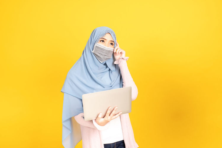 Midsection of person holding smart phone against yellow background