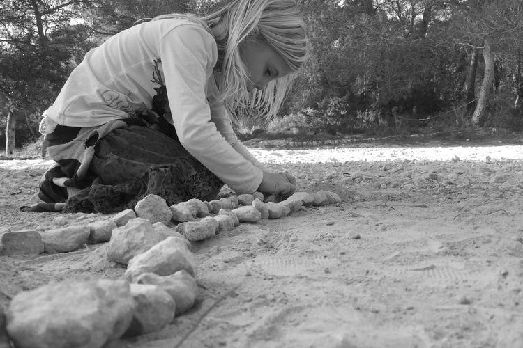 Side View Of Girls Arranging Rocks On Field
