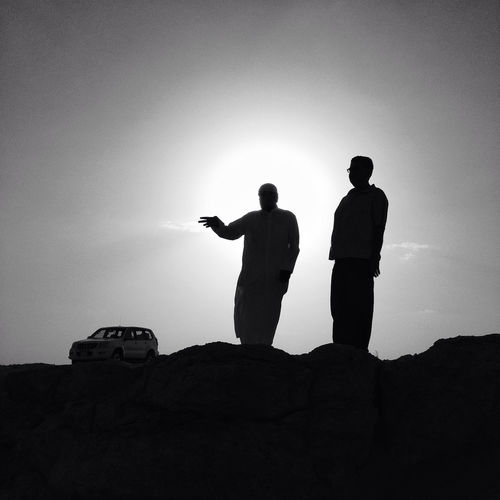 Silhouette men standing on rock against clear sky