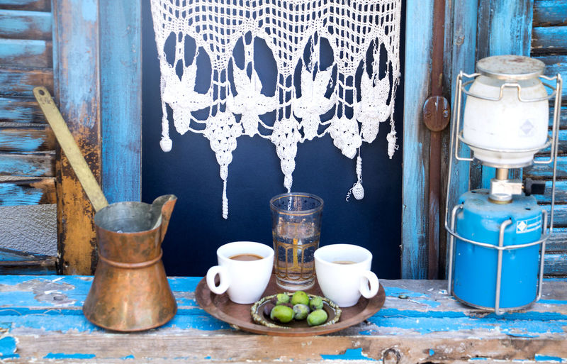 typical greek window with a briki and two mocha cups Coffee Time Greek Coffee  Mediterranean  Shutters Blue Bottle Briki Curtain Day Food Food And Drink Freshness Gas Lamp Glass Household Equipment Indoors  Mocha Cup No People Olives Still Life Typical Greek Vase Window View Windowsill Wood - Material