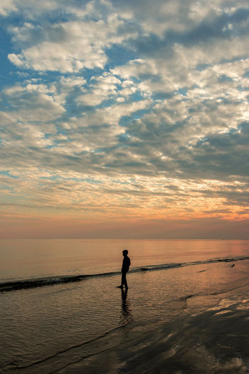 Silhouette man standing on beach against sky during sunset