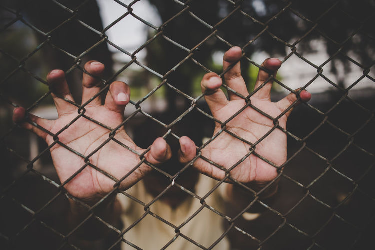 Cropped image of man touching metal fence