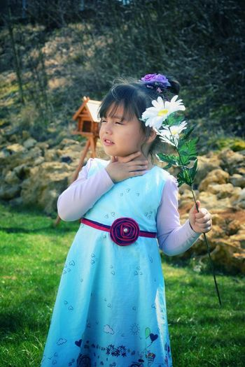 Cute girl touching her neck while holding flowers in yard