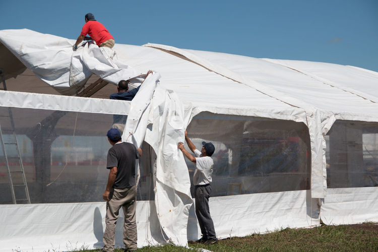 People covering greenhouse roof against clear sky