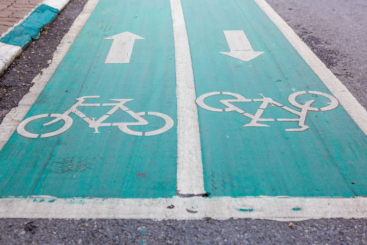 Blue bike lens on the street background Bicycle Lane Bike Blue City Communication Day Direction Guidance High Angle View Information Information Sign Lens Marking No People Outdoors Road Road Marking Road Sign Sign Street Symbol Text Transportation Turquoise Colored