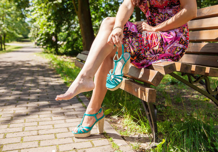 Low section of young woman holding high heels while sitting on bench at park