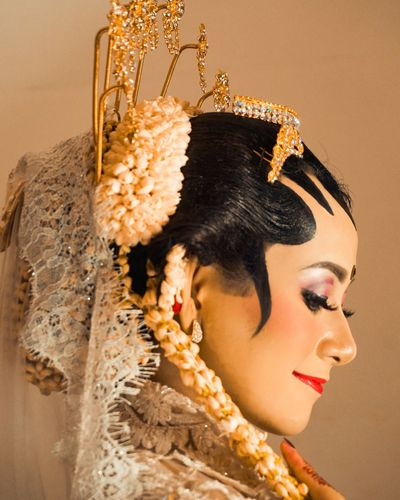 Side view of bride wearing jewelry against brown background