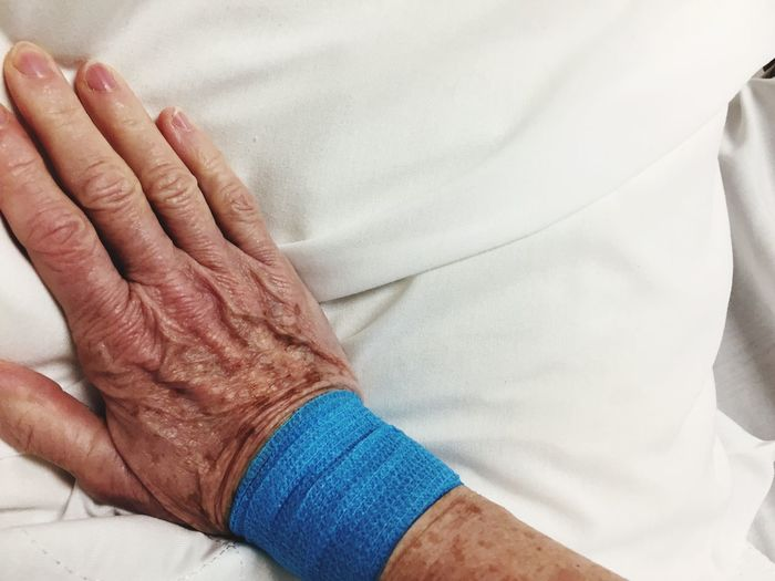 Midsection Of Senior Person Lying On Bed In Hospital