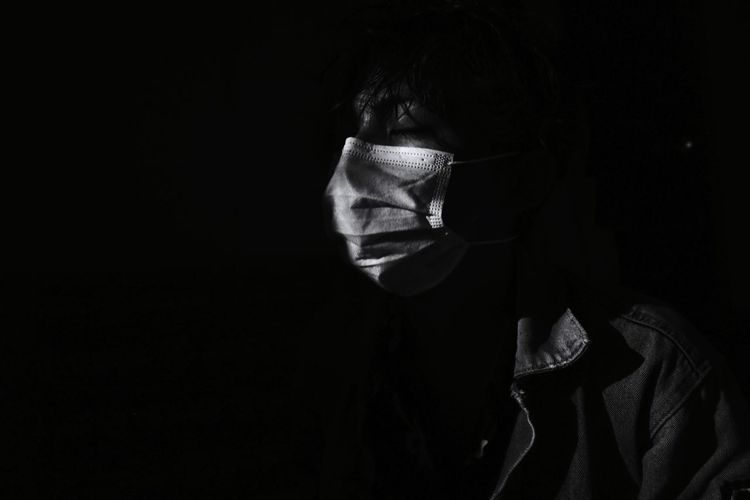 Portrait of a man wearing a mask with a hopeful expression on a black background
