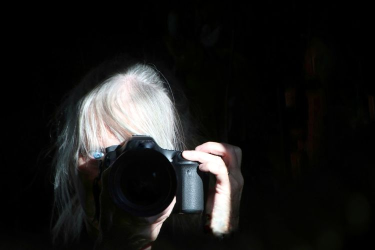 Woman photographing on black background